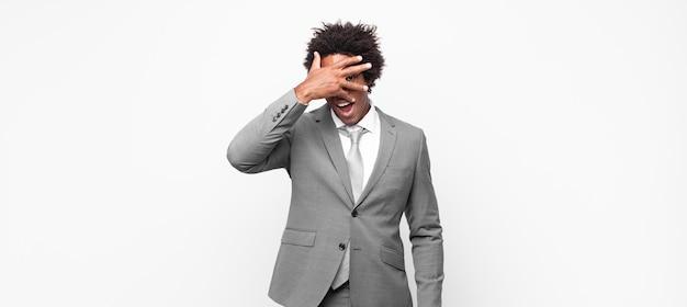 Czarny biznesmen afro wyglądający na zszokowanego, przestraszonego lub przerażonego, zakrywający twarz dłonią i zaglądający między palce