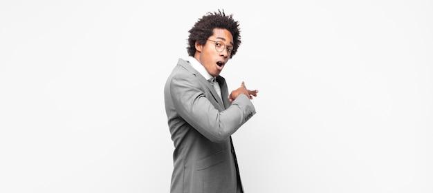 Czarny biznesmen afro, zszokowany i zaskoczony, wskazujący na skopiowanie miejsca z boku ze zdumionym spojrzeniem z otwartymi ustami