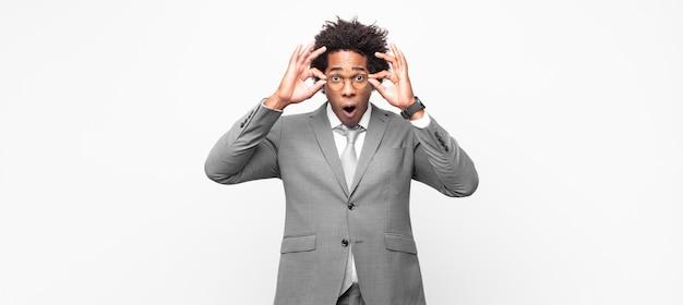 Czarny biznesmen afro, zszokowany, zdumiony i zaskoczony, trzymający okulary ze zdumionym, niedowierzającym spojrzeniem