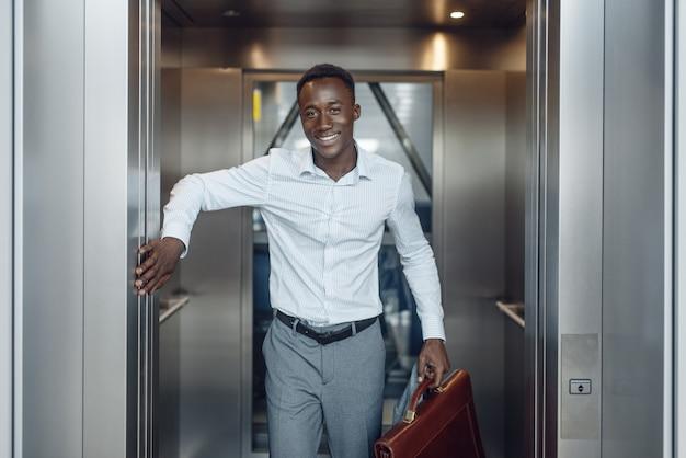 Czarny biznesmen idzie do windy w biurowcu. sukcesy biznesmena, murzyn w wizytowym, centrum handlowym