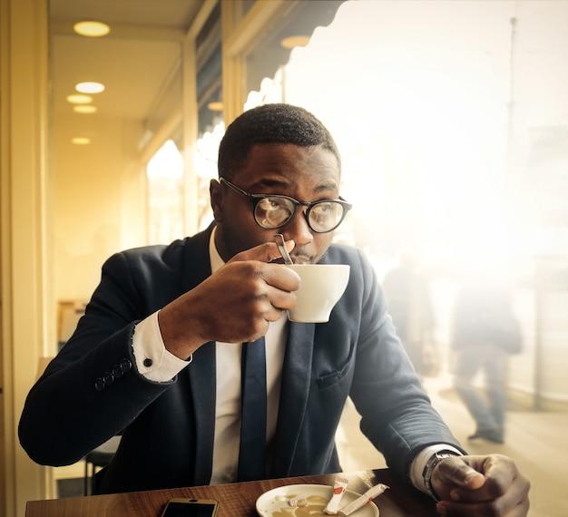 Czarny biznesmen pije kawę
