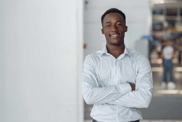 Czarny biznesmen pozuje w biurowcu. sukcesy biznesmena, murzyn w wizytowym, centrum handlowym