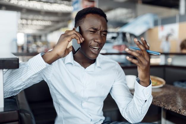 Czarny biznesmen rozmawia przez telefon, salon samochodowy. sukcesy biznesmena na motor show, murzyn w wizytowym