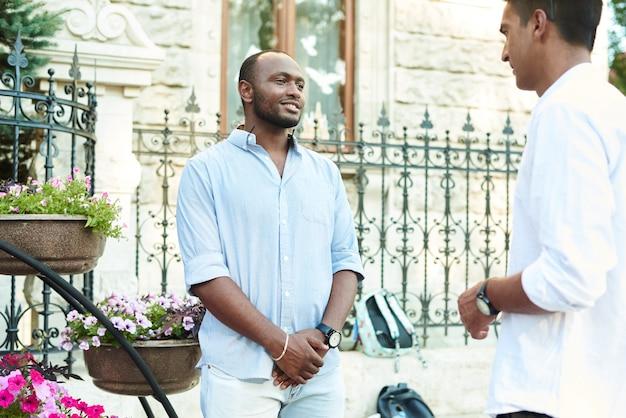 Czarny biznesmen rozmawia w nieformalnym otoczeniu z partnerem biznesowym na ulicy miasta.