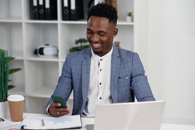Czarny biznesmen surfuje strony internetowe na smartphone, ma przerwę przy pracą w nowożytnym biurze.