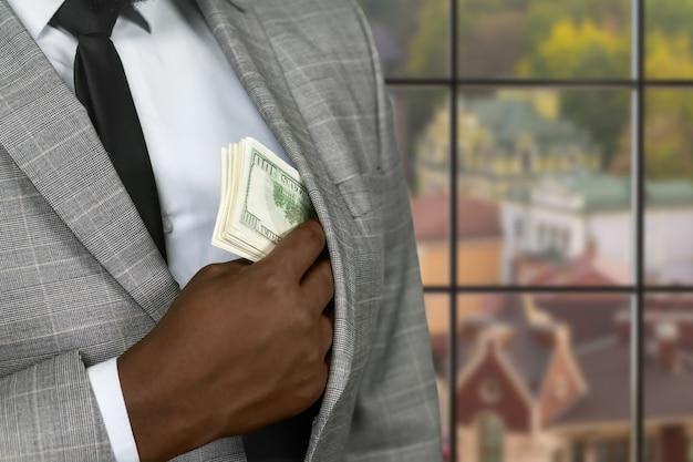Czarny biznesmen ukrywa gotówkę. zamożny człowiek na tle miejskim. przestępca jest zawsze ostrożny. oderwanie się od prawa.