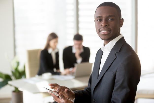 Czarny biznesmen używa cyfrową pastylkę na spotkaniu
