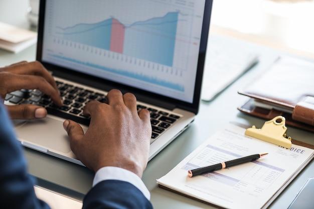 Czarny biznesmen używa komputerowego laptop