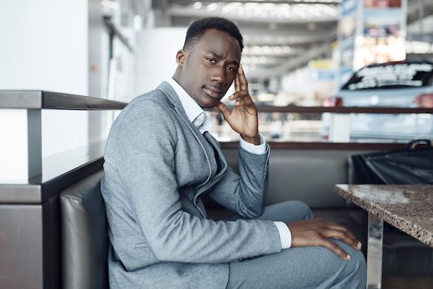 Czarny biznesmen w garniturze siedzi w salonie samochodowym. przedsiębiorca odnoszący sukcesy na targach motoryzacyjnych, mężczyzna w stroju wizytowym, poczekalnia