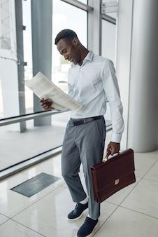 Czarny biznesmen z teczką do czytania gazety, centrum handlowe. sukcesy biznesmena, murzyn w wizytowym, centrum handlowym