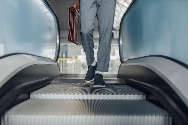 Czarny biznesmen z teczką na schodach ruchomych w centrum handlowym. sukcesy biznesmena, murzyn w wizytowym, centrum handlowym