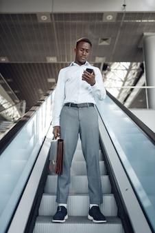 Czarny biznesmen z teczką rozmawia przez telefon na schodach ruchomych w centrum handlowym. sukcesy biznesmena, murzyn w wizytowym, centrum handlowym