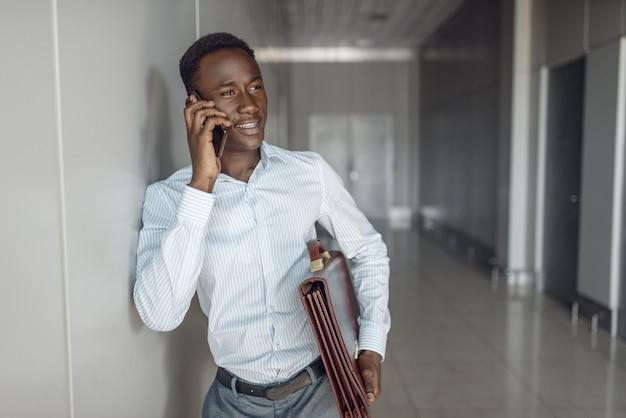Czarny biznesmen z teczką rozmawia przez telefon w biurze na korytarzu. sukcesy biznesmen negocjuje na korytarzu, czarny mężczyzna w wizytowym stroju