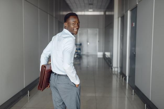 Czarny biznesmen z teczką w hali biurowej. biznesmena sukcesu idąc korytarzem, czarny mężczyzna w wizytowym
