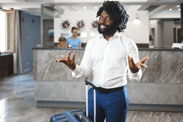 Czarny biznesmen z zapakowanym bagażem stojący w holu hotelu