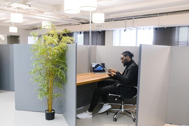 Czarny biznesmen za pomocą laptopa do analizy zapasów danych