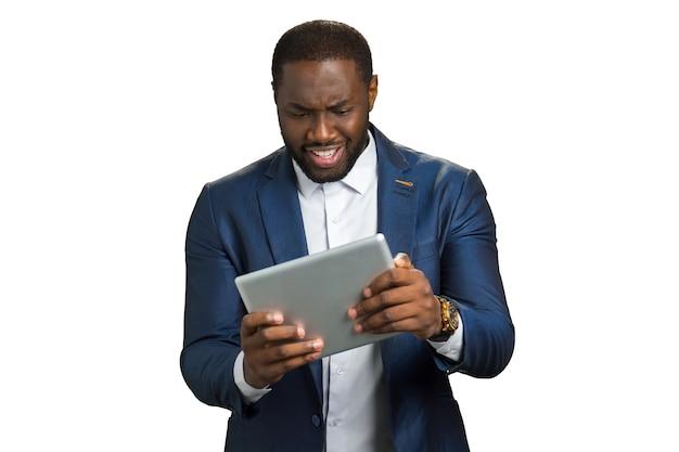 Czarny biznesmen zaskoczony, patrząc na komputer typu tablet. amerykański menedżer trzyma tablet z ekranem dotykowym i uśmiecha się ze zdumieniem.