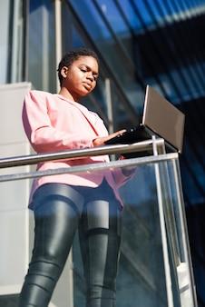 Czarny bizneswoman stoi blisko biznesowego budynku biurowego pracuje z laptopem.