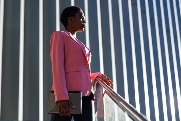 Czarny bizneswoman stoi blisko biznesowego budynku biurowego.