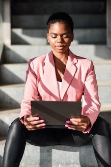 Czarny bizneswomanu obsiadanie na miastowych krokach pracuje z laptopem.