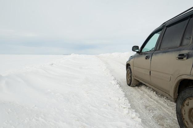 Czarny brudny samochód na zimowej drodze oczyszczonej ze śniegu. pojęcie bezpiecznego ruchu drogowego zimą.
