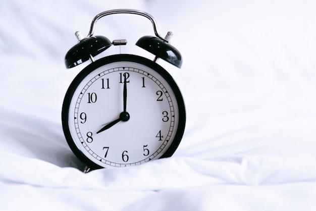 Czarny budzik na białym łóżku. pojęcie czasu i godzin. motyw wnętrza i obiektu