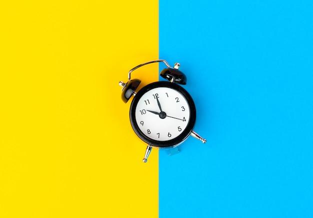 Czarny budzik na bloku koloru żółtym i niebieskim