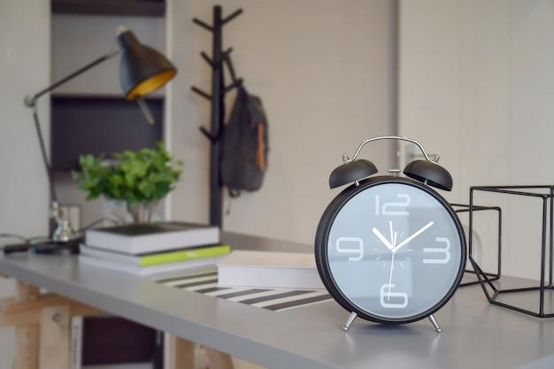 Czarny budzik na stole roboczym w domu