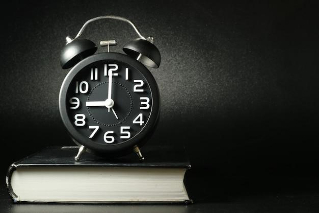 Czarny budzik umieszczony na grubej książce.