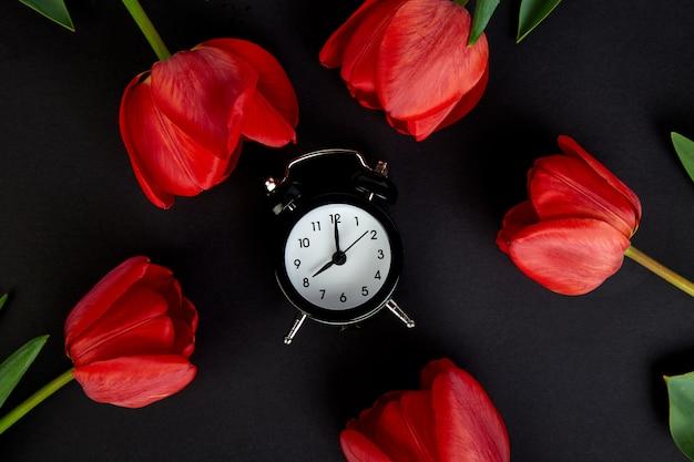 Czarny budzik w pobliżu bukiet czerwonych tulipanów