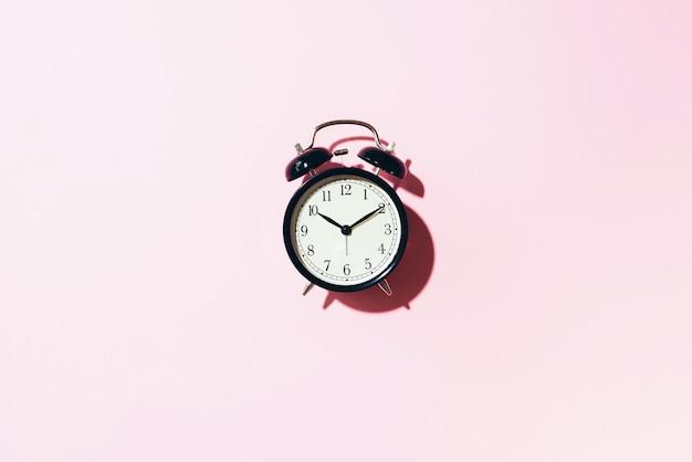 Czarny budzik z twardym cieniem na różowym tle.