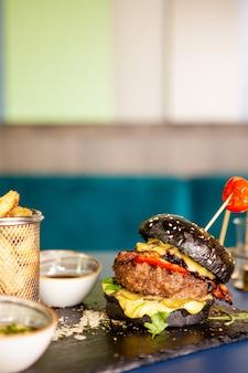 Czarny burger z mięsem wołowym i frytkami. smaczny apetyczny
