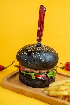 Czarny burger z nożem w środku i frytkami