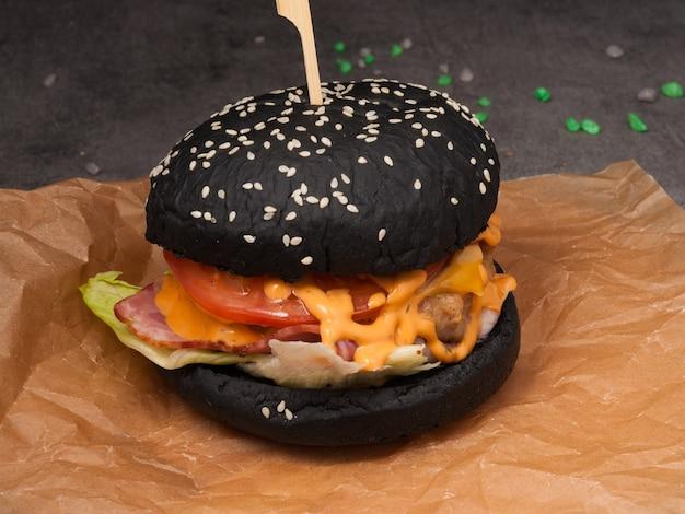 Czarny burger z pomidorem bekonowym, panierowanym kurczakiem i sosem serowym