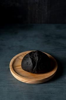 Czarny burger z wysokim kątem na drewnianej tacy