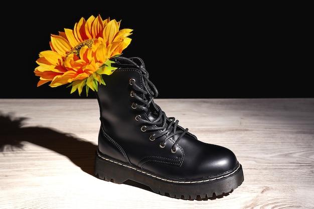 Czarny but z żółtym kwiatkiem na jasnym podłożu