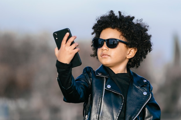 Czarny chłopak z afro włosami, okularami przeciwsłonecznymi i skórzaną kurtką, robiący selfie ze swoim smartfonem. na tle parku. obraz z copyspace. koncepcja dzieci, smartfonów i czarnych ludzi