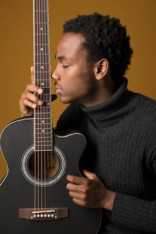 Czarny chłopiec gra na gitarze