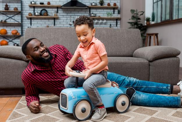 Czarny chłopiec jazdy samochodem zabawki z ojcem