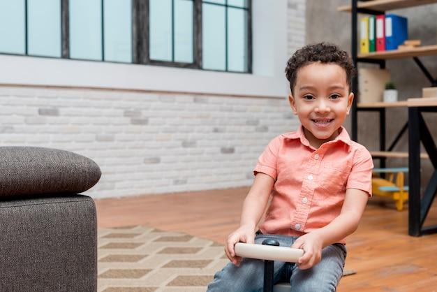 Czarny chłopiec jazdy samochodem zabawki