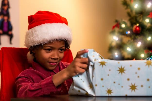 Czarny chłopiec otwierając świąteczny prezent.