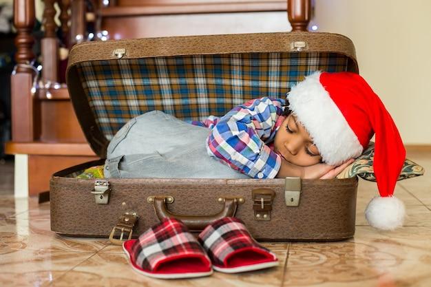Czarny chłopiec śpi w walizce. mały mikołaj śpi w walizce. nowy dzień czeka. definicja spokoju.
