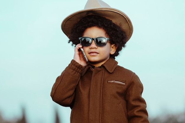 Czarny chłopiec w kowbojskim kapeluszu i okularach przeciwsłonecznych, rozmawia przez telefon komórkowy. na tle parku. koncepcja dzieci, smartfonów i czarnych ludzi