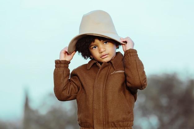 Czarny chłopiec w kowbojskim kapeluszu, patrząc w kamerę. na tle parku. . obraz z copyspace. koncepcja dzieci i czarnych ludzi