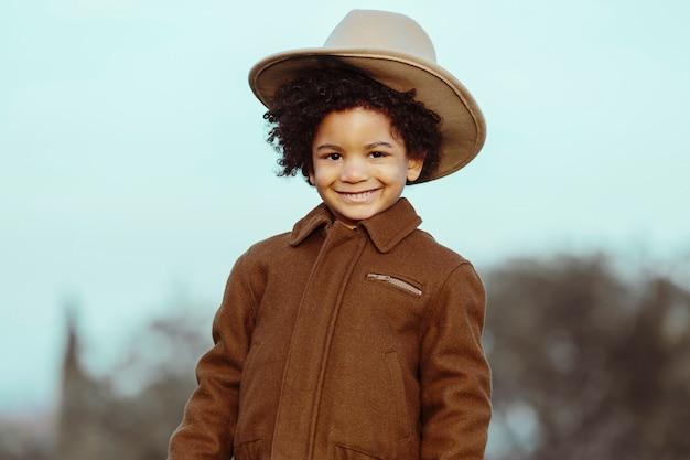 Czarny chłopiec w kowbojskim kapeluszu, uśmiechnięty. na tle parku. . obraz z copyspace. koncepcja dzieci i czarnych ludzi