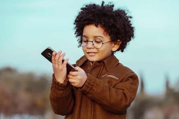 Czarny chłopiec z afro włosami i okularami, używając swojego smartfona, uśmiechnięty, odwracając wzrok. na tle parku. obraz z copyspace. koncepcja dzieci, smartfonów i czarnych ludzi