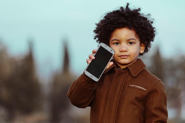 Czarny chłopiec z afro włosami, pokazując swój telefon komórkowy. na tle parku. koncepcja dzieci, smartfonów i czarnych ludzi. obraz z copyspace