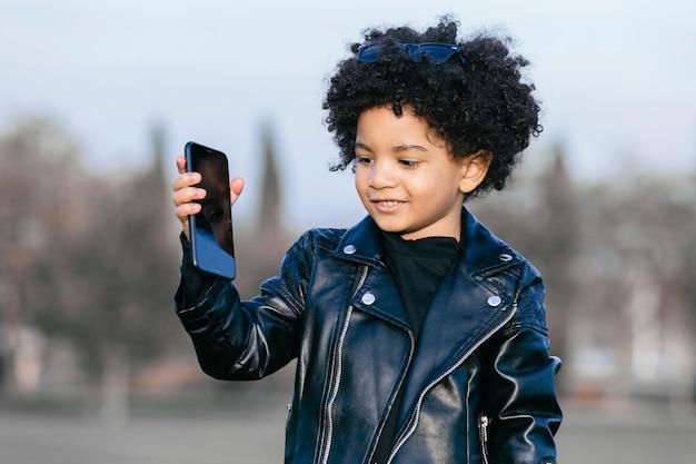 Czarny chłopiec z włosami afro i skórzaną kurtką, pokazujący swój smartfon. na tle parku. obraz z copyspace. koncepcja dzieci, smartfonów i czarnych ludzi