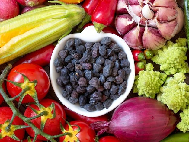 Czarny ciecierzyca w pucharze między surowych warzyw odgórnym widokiem