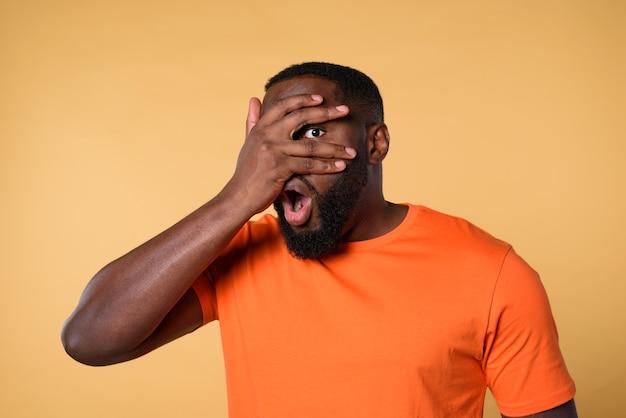 Czarny ciekawy człowiek próbuje coś obejrzeć przez rękę. pomarańczowa ściana